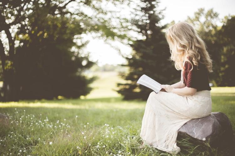 Une jeune fille blonde vue de profil lit un livre assise sur une pierre, dans une clairière.